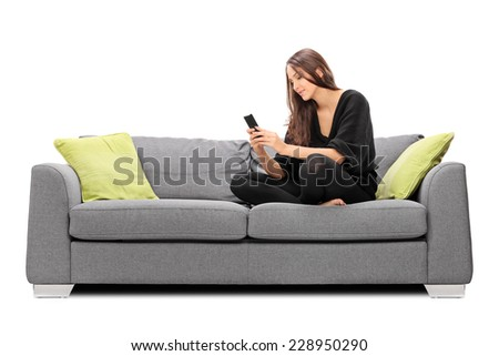 Young woman playing on her cell phone seated on a sofa isolated on white background - stock photo