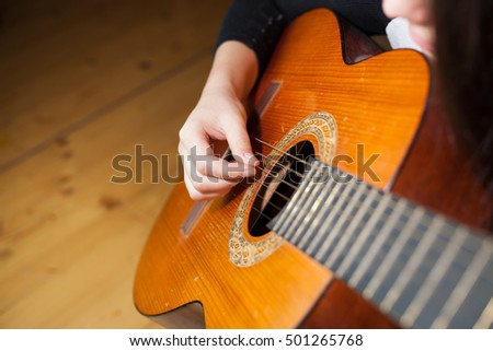 Young woman playing on her guitar and relaxing (focus on finger)