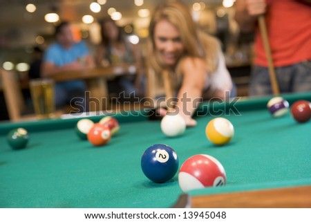 Young woman playing pool in a bar (focus on pool table) - stock photo