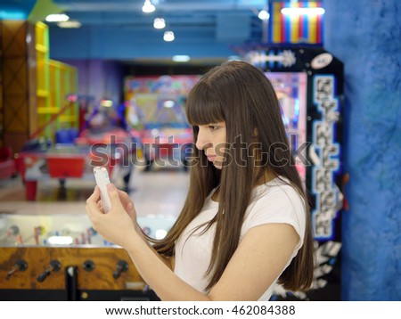 Young woman playing popular smartphone game in mall