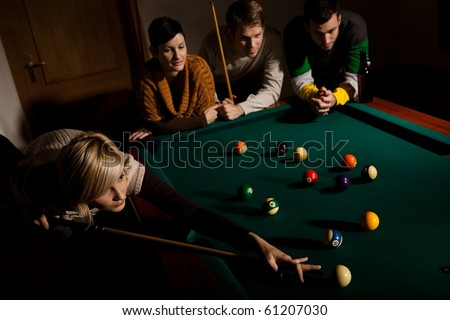 Young woman playing snooker, aiming at white ball with cue, other people watching.? - stock photo