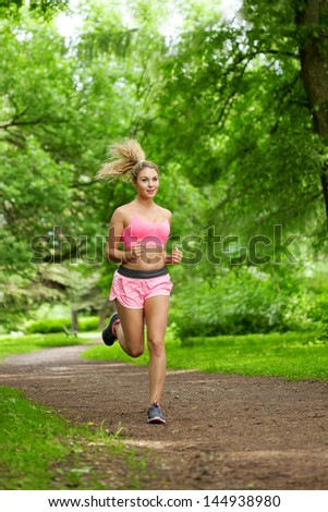 Young woman playing sports, running in the park