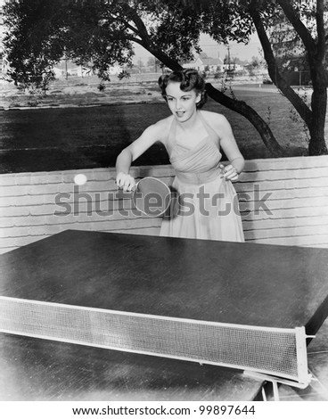 Young woman playing table tennis - stock photo
