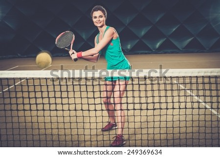 Young woman playing tennis indoors  - stock photo