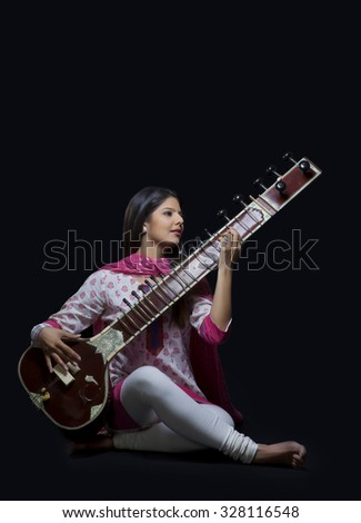 Young woman playing the sitar - stock photo