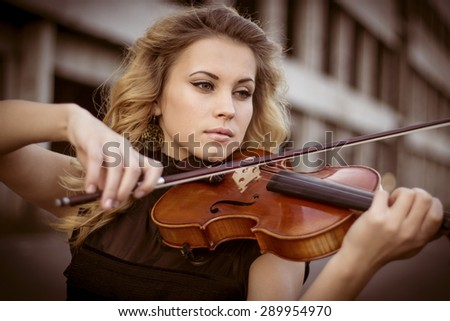 Young woman playing the violin at outdoors. Shallow depth of field.