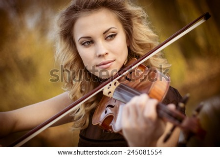 Young woman playing the violin at park. Shallow depth of field. - stock photo