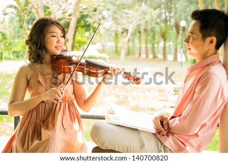 Young woman playing violin with her boyfriend in garden - stock photo