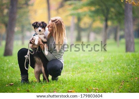 Young woman playing with Australian Shepherd dog outdoors in the park.  - stock photo