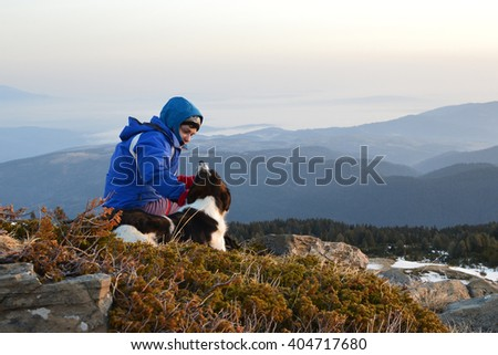 Young woman playing with dog at sunrise high in the mountain, Rila Mountains, Bulgaria - stock photo