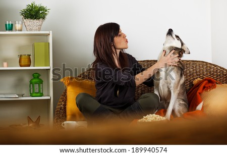 Young woman playing with her dog - stock photo