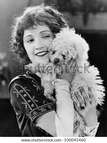 Young woman playing with her dog and smiling - stock photo