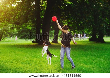 Young woman playing with her dog in a park. She is holding a red disc. Dog tries to catch it. The woman smiles.A warm summer day. Dense green grass. Vacationers people in the background. - stock photo