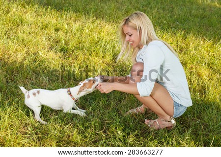 Young woman playing with her dog. Selective focus on woman face