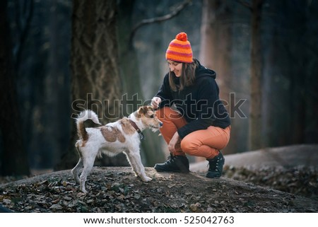 Young woman playing with her fox terrier in the forest. Best friend concept.