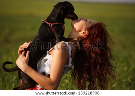 Young woman playing with her little dog - stock photo