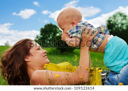 young woman playing with her son in the park