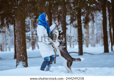 young woman playing with husky dog in the snow, Winter fun - stock photo