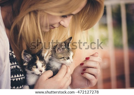 Young woman playing with two kittens outside