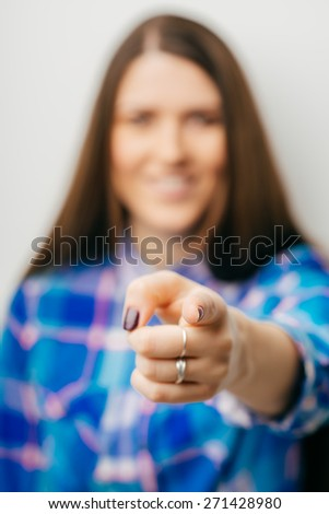 young  woman pointing at someone gesture with finger - stock photo