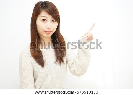 Young woman pointing something with white  background