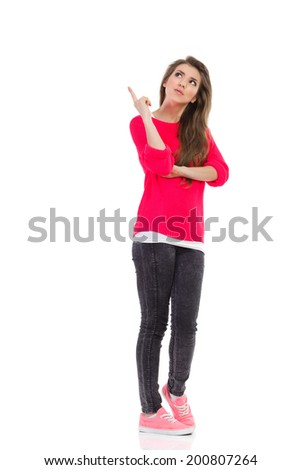 Young woman pointing up at empty space. Full length studio shot isolated on white. - stock photo