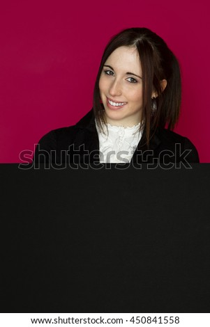 Young woman poping out from behind a black board