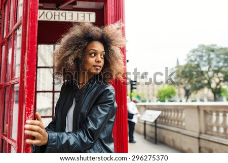 Young woman portrait close to red telephone box in London. - stock photo