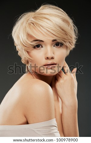 Young woman portrait. Closeup beauty studio shoot. Healthy clean skin and perfect makeup on beautiful face of white model with short blonde hair. Beautiful girl. - stock photo