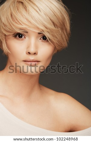 Young woman portrait. Closeup beauty studio shoot. Healthy clean skin and perfect makeup on beautiful face of white model with short blonde hair. - stock photo