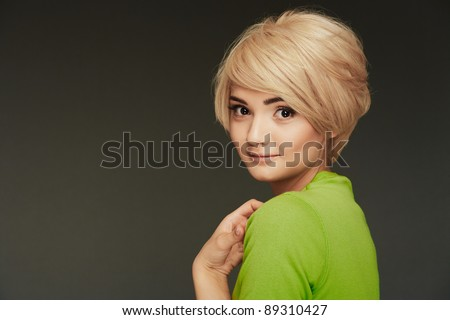 Young woman portrait. Closeup beauty studio shoot. Healthy clean skin and perfect makeup on beautiful face of white model with short blonde hair. Beautiful girl. Posing fashion model. - stock photo