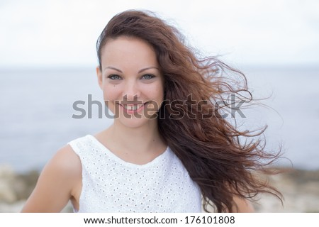 Young woman portrait. Curly girl in white looks at camera smiling - stock photo