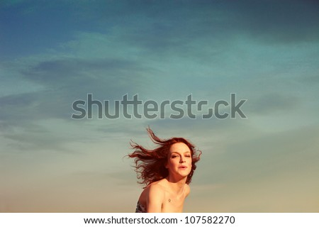 young woman portrait in motion on sky background summer day retro colors - stock photo