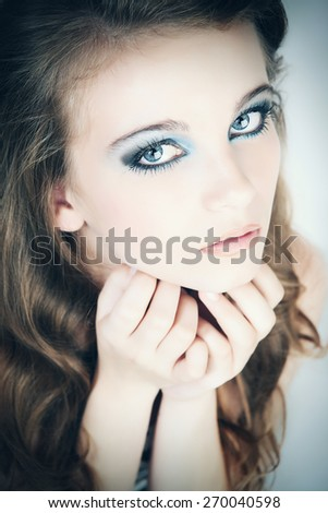 Young woman portrait in studio. Business woman portrait isolated over blue background. - stock photo