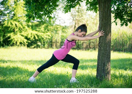 Young woman portrait stretching her legs against a tree outdoors in a park.  - stock photo