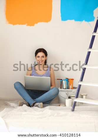 Young woman portrait while painting new apartment ,sitting with laptop - stock photo