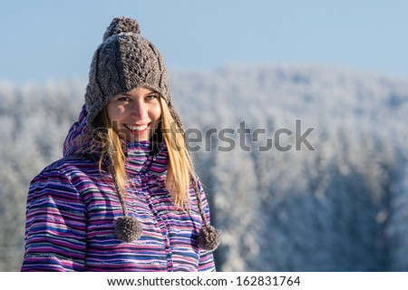 Young woman portrait winter mountains snow smiling sunny countryside - stock photo