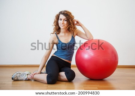Young woman portrait with ball in the gym.  - stock photo