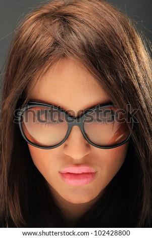 young woman portrait with big fashion sunglasses, studio shot - stock photo