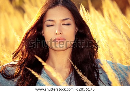 young woman portrait with eyes closed enjoy in autumn sun on yellow field