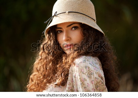young woman portrait with hat outdoor in park summer day sunset - stock photo