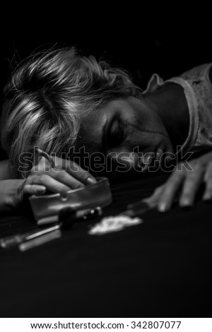 Young woman poses as an unconscious drug addict with the drug and syringe, Black and White.