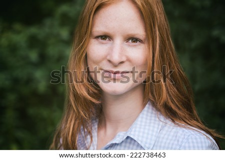 Young woman poses for a closeup portrait before green vegetation in a park.