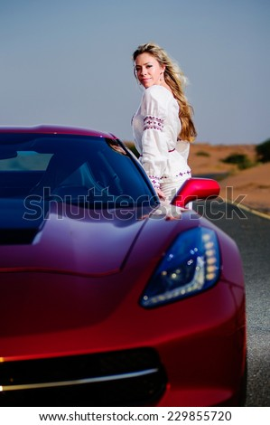 Young woman poses near car in desert in sunset.