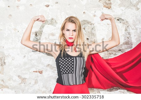 Young woman posing as superhero or wonderwoman - stock photo