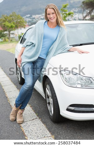Young woman posing beside her car - stock photo