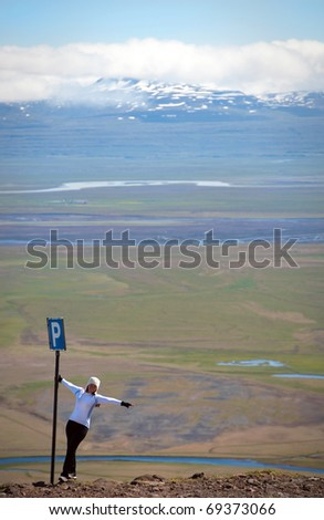 young woman posing by the parking sing, amazing Icelandic landscape in background - stock photo