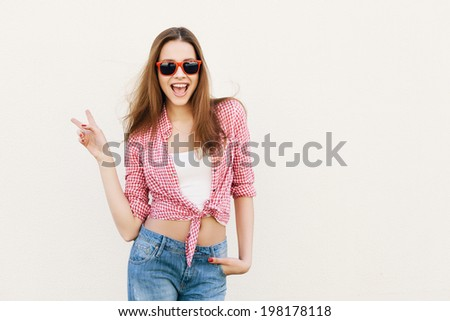 Young woman posing by the wall. Girl showing gesture. Not isolated - stock photo