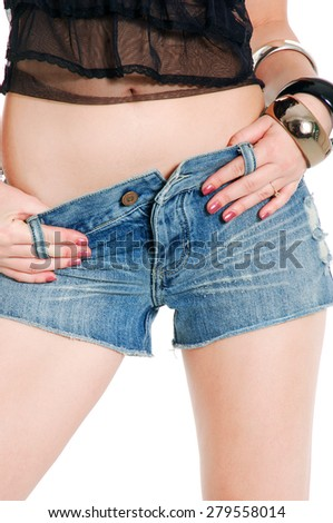 young woman posing in blue shorts jeans on white background - stock photo