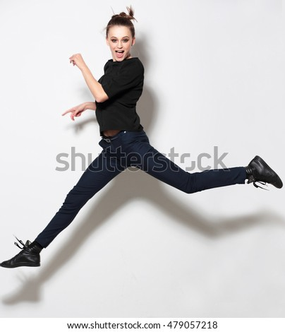 Young woman posing in full body and smiling. Clothing, fashion. Jump, movement.